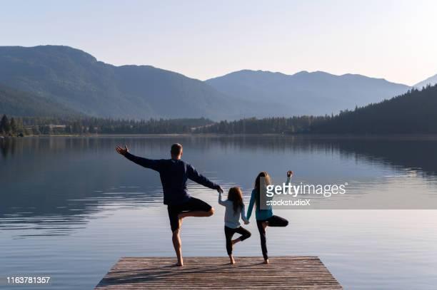 familie beoefenen yoga buitenshuis - mindfulness stockfoto's en -beelden