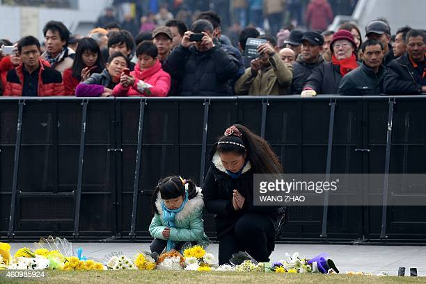 A family pray for the victims at the site of the New Year's Eve stampede in Shanghai on January 3 2015 The New Year's stampede just before midnight...