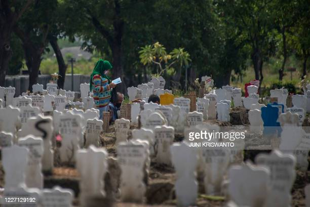 Family pray for their relative at a burial site for victims of the COVID-19 coronavirus at Keputih cemetery in Surabaya, East Java on July 15, 2020.