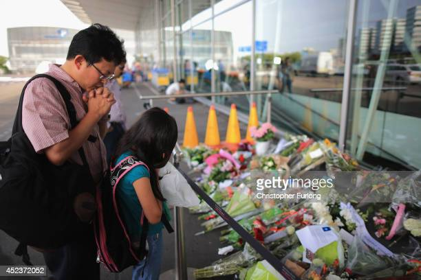 A family pray next to floral tributes at the entrance to Schiphol Airport in memory of the victims of Malaysia Airlines flight MH17 on July 19 2014...