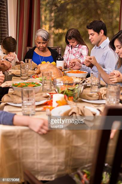 family praying before thanksgiving dinner at grandmother's home. - national day of prayer stock photos and pictures