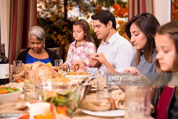 family praying around table - 612×408