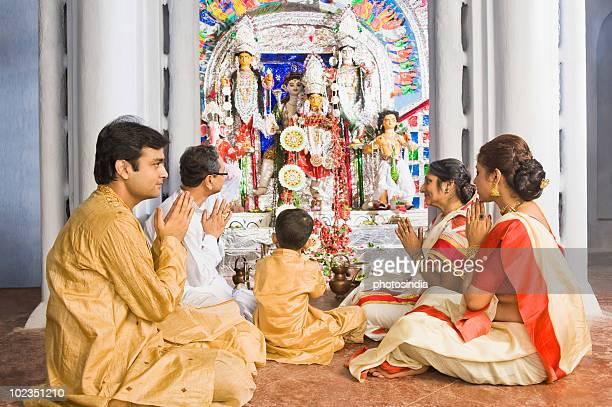 family praying in a temple - gelovige stockfoto's en -beelden