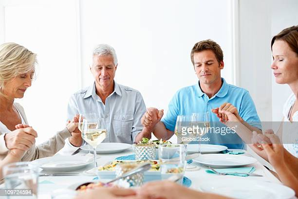 family praying together before their meal - national day of prayer stock photos and pictures