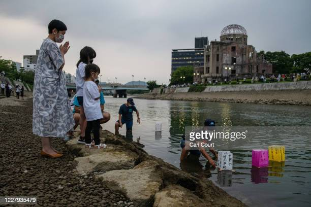 A family prays as paper lanterns are floated on the Tenma River to mark the 75th anniversary of the Hiroshima atomic bombing in a lantern ceremony...