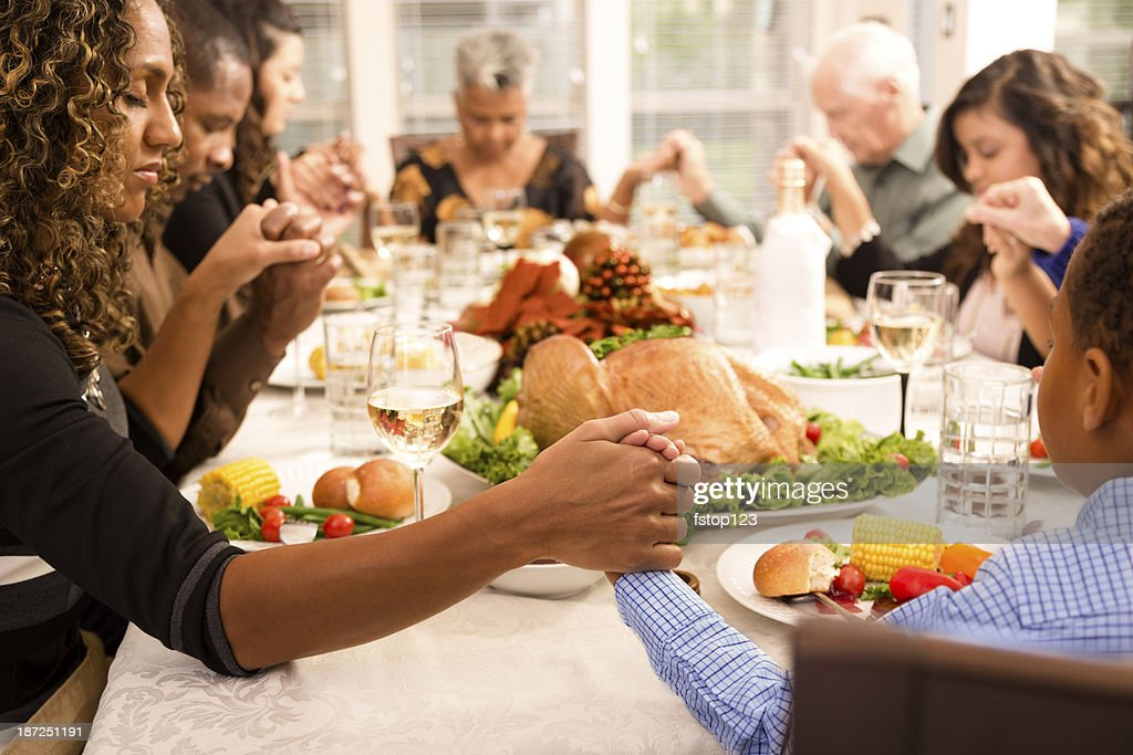 Family Prays At Thanksgiving Table Holding Hands