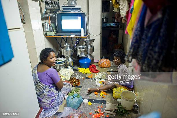 A family prepares flowers for the temple while watching TV in their home in Dharavi November 4 2011 in Mumbai India Dharavi Asia's largest slum...