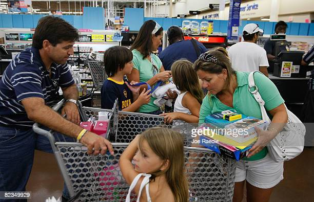 A family prepares their goods to go through the cash register as they as they make purchases at a WalMart Store August 14 2008 in North Miami Florida...