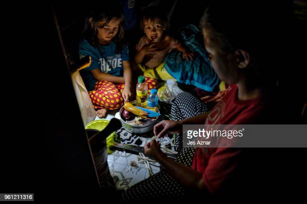 A family prepares their last meal before fasting for Ramadan inside their tent shelter in Sarimanok tent city on May 15 2018 in Marawi Philippines...