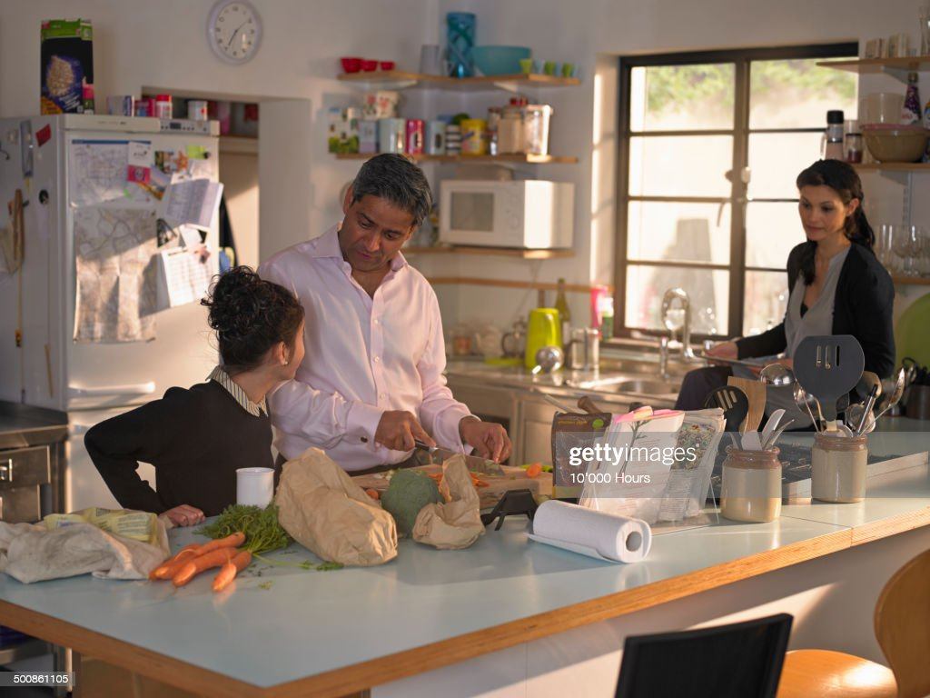 Family preparing a meal from a recipe on an iPad : Stockfoto