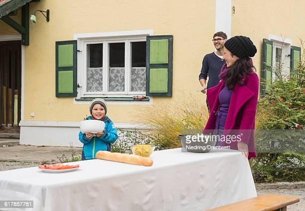 'Family preparing a picnic table outside at farmhouse, Bavaria, Germany'