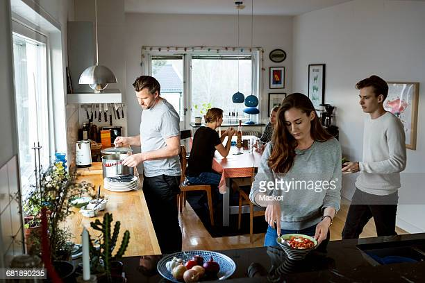 family preparing food in kitchen - weekday stock pictures, royalty-free photos & images