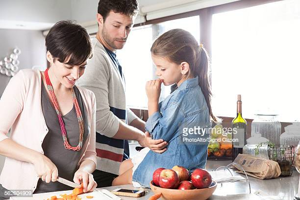 Family preparing food together in kitchen