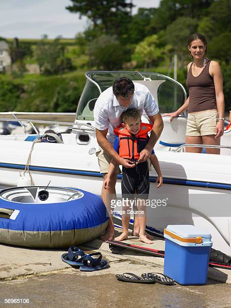 family preparing for boat trip - life jacket stock pictures, royalty-free photos & images