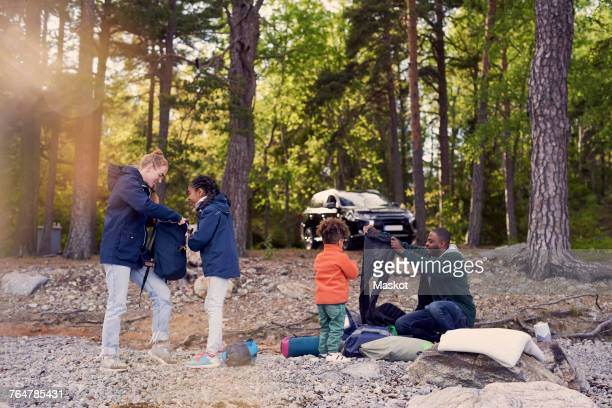 Family preparing for camping against trees