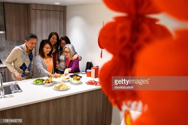 familie die voor chinese nieuwjaar voorbereidingen treft - 20 29 years stockfoto's en -beelden