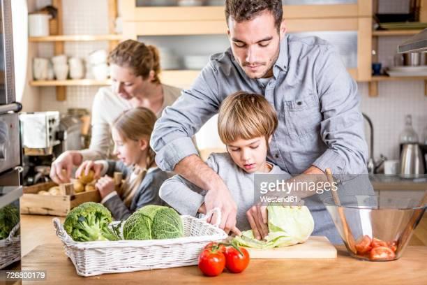 Family preparing salad in kitchen
