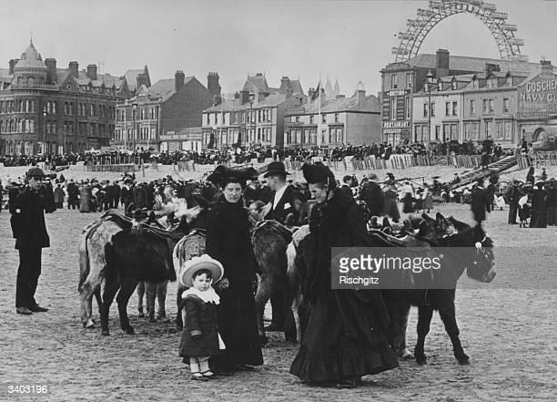 A family preparing to take a donkey ride on Blackpool beach Lancashire