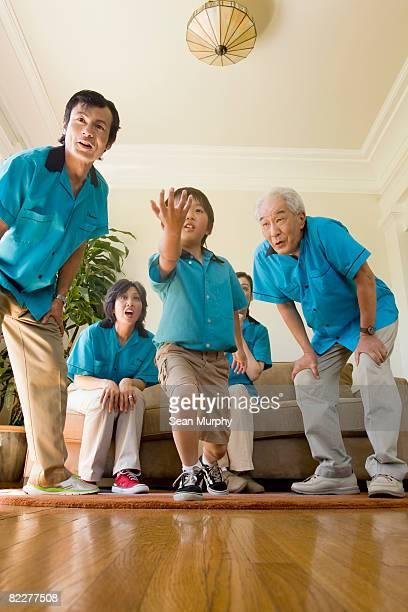 Family pretending to bowl in living room