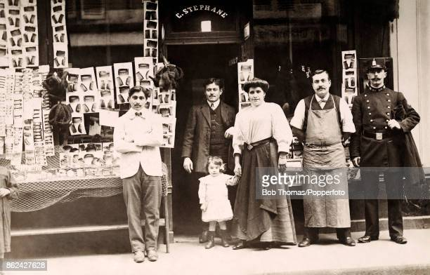 Family proprietors and staff standing in front of a shop that sells combs and barrettes in France circa 1900