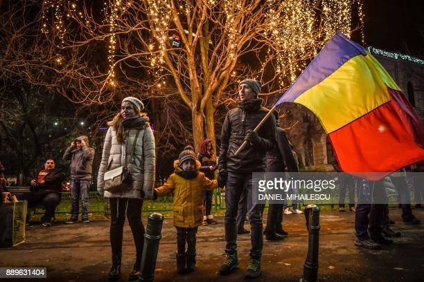 A family protests in front of the Romanian Government headquarters in Bucharest on December 10 2017 Around 7000 Romanians took to the streets on...
