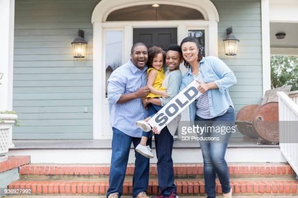family proud of their new home - new home stock pictures, royalty-free photos & images