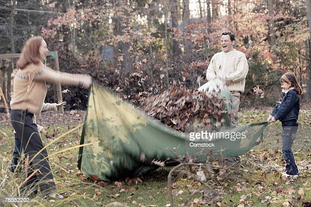 Family pulling leaves in blanket