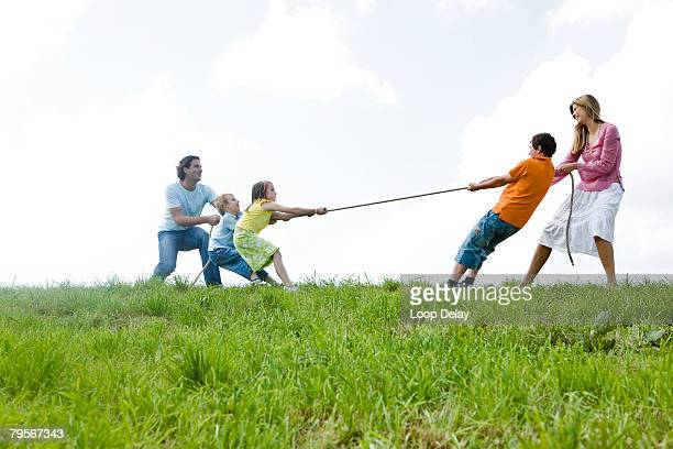 Family with children playing tug-of-war in field, low angle view