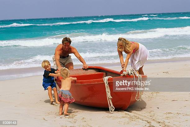 family pulling rowboat out to ocean - generic location stock pictures, royalty-free photos & images