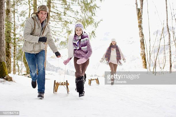 Family pulling sleds through snow