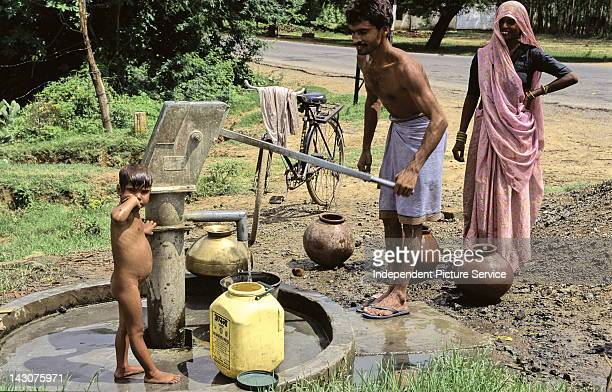 Family pumping clean drinking water from a new well in India
