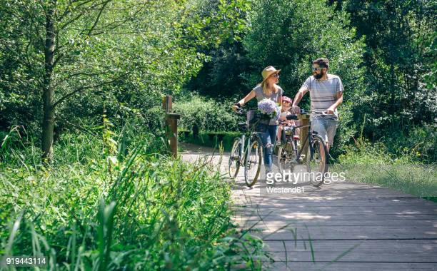 family pushing bicycles on wooden walkway - small group of people stock pictures, royalty-free photos & images