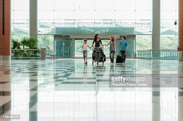 Family pushing luggage cart in airport lobby