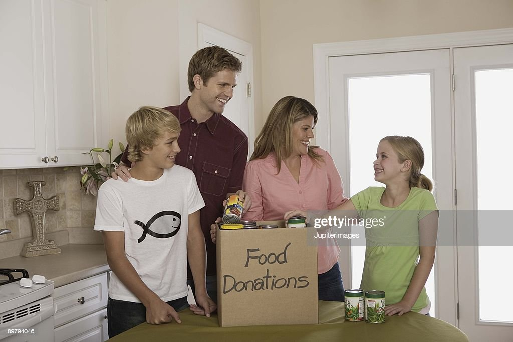 Family putting canned food in donations box indoors : Stock Photo