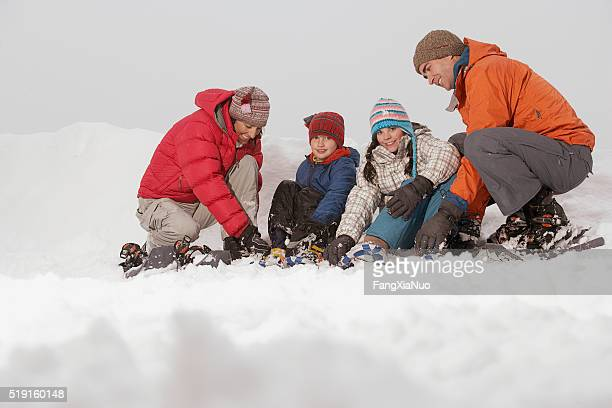 Family putting on snow shoes