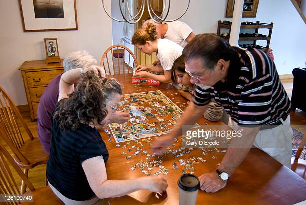 Family putting together a puzzle on the dinning room table, Martha's Vineyard, MA