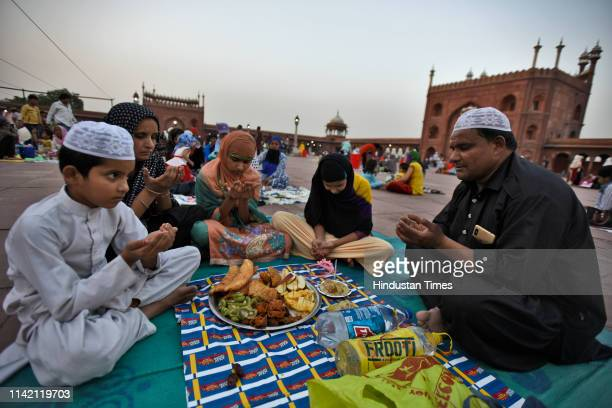 A family raises their hands to make Dua before breaking their fast on the first day of the holy fasting month of Ramadan at Jama Masjid on May 7 2019...