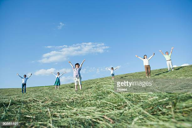Family raising arms on grass