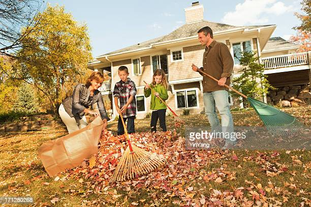 family raking autumn leaves, outdoors team together in home yard - rake stock pictures, royalty-free photos & images