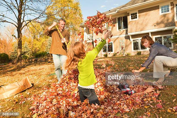 Family Raking Autumn Leaves, Outdoors Team Together in Home Yard
