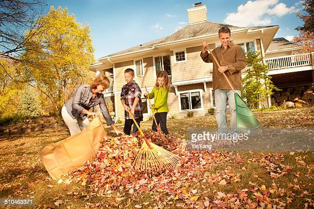 family raking leaves together in autumn - rake stock pictures, royalty-free photos & images