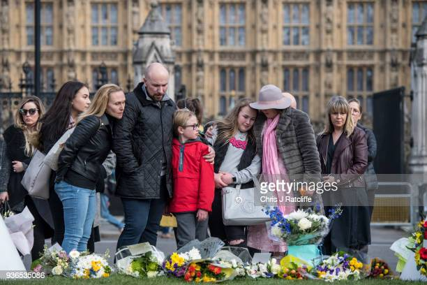A family react after leaving floral tributes in Parliament Square on the first anniversary of the Westminster Bridge terror attack on March 22 2018...
