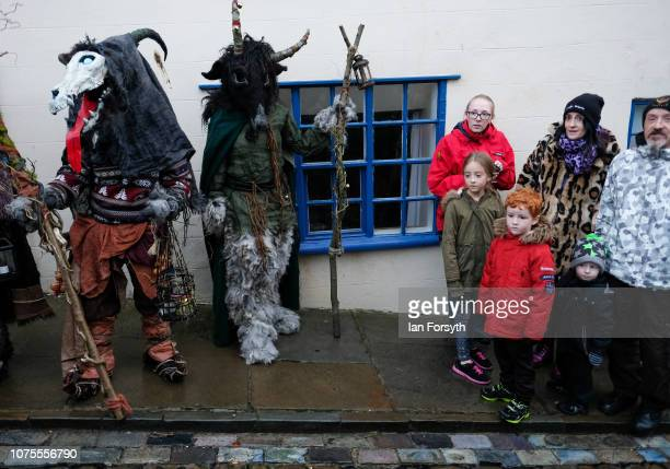 A family react as they stand next to participants during the annual Whitby Krampus parade on December 01 2018 in Whitby England The Krampus is a...