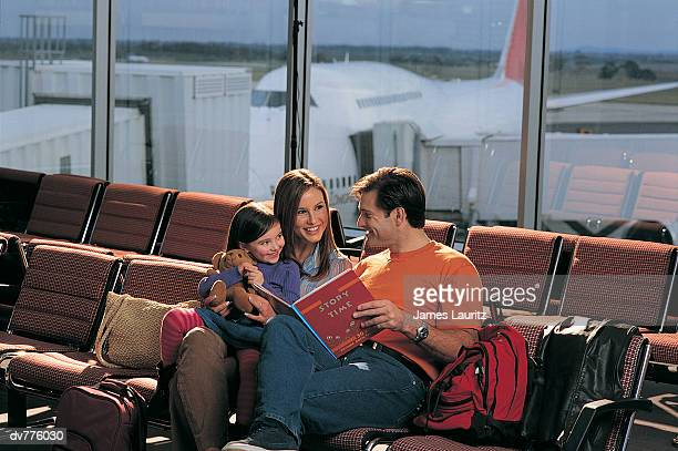 Family Reading a Book in An Airport Lounge