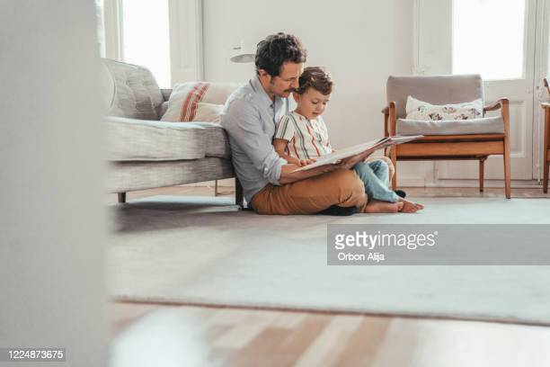 famiglia che legge un libro - figlio maschio foto e immagini stock
