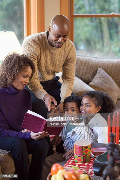 Family reading book during Kwanzaa