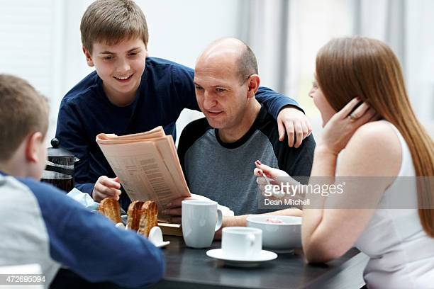 Family reading newspaper at breakfast table