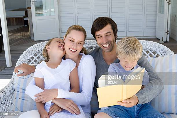 Family reading on sofa together