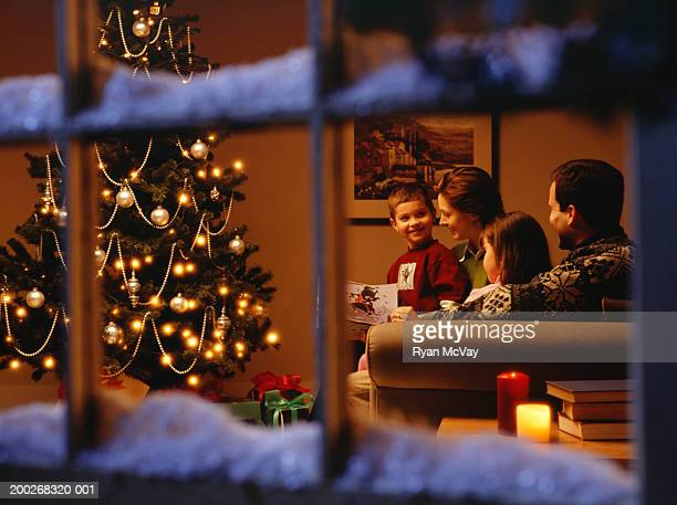 Family reading together on sofa at Christmas time, viewed through window