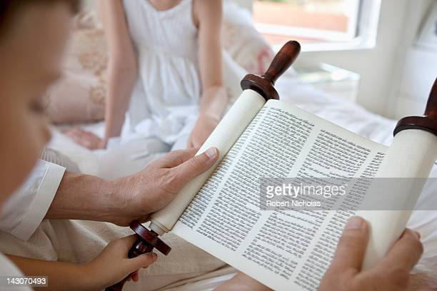 family reading torah scrolls together - judendom bildbanksfoton och bilder